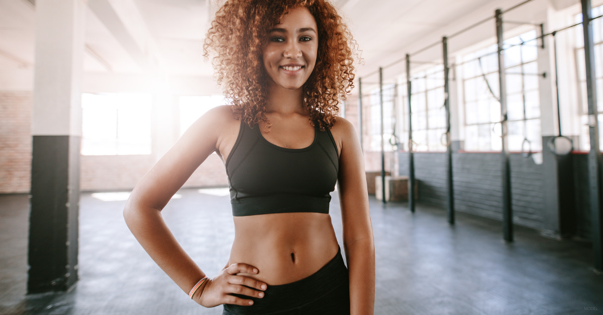 A woman poses at the gym and is happy with her tummy tuck results.