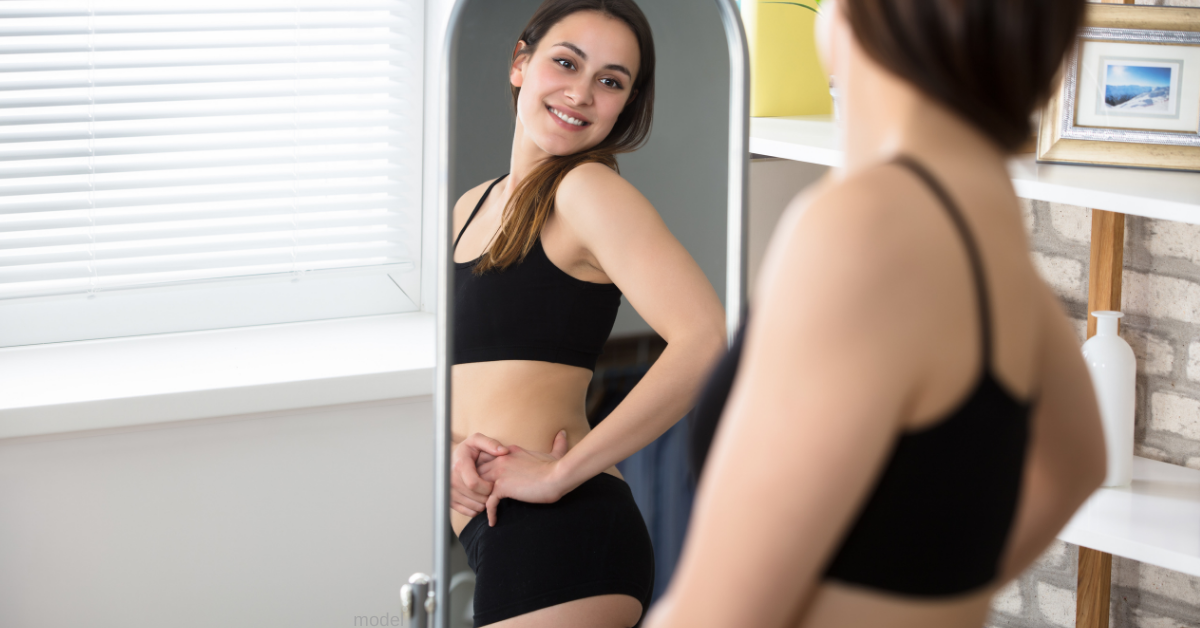 Woman looks in mirror at tummy tuck results