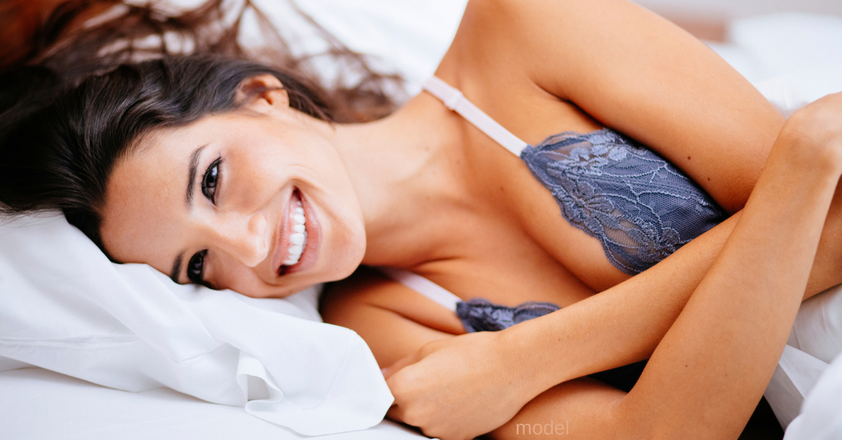 Woman smiling and relaxing on bed